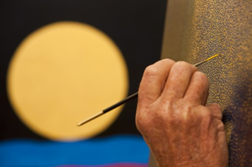 A simple device of using a finished picture hanging in the background to offset the foreground detail of the artist at work.