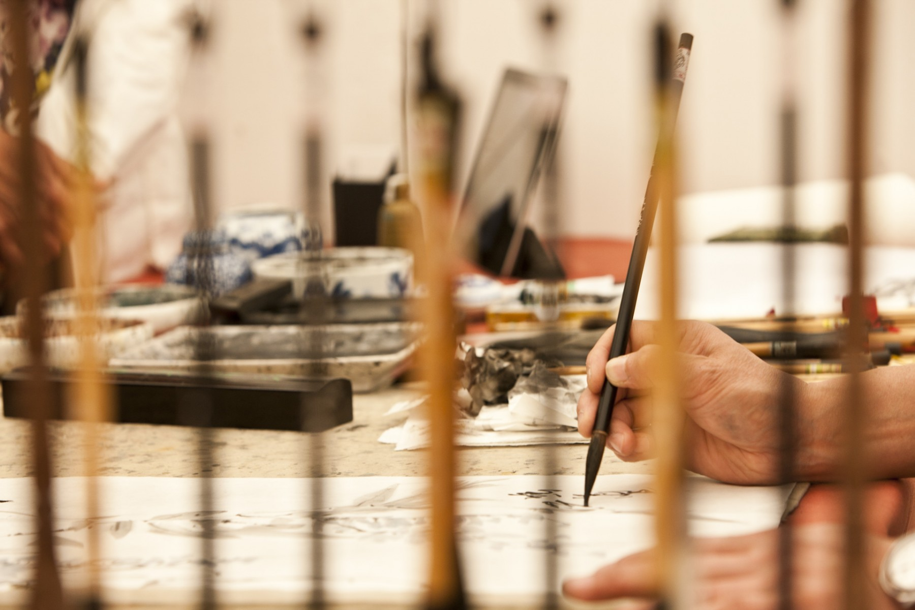 Traditional Chinese brush painting demonstrated by Shuhua Jin. Here I used a rack of paint brushes to frame my image giving it a sense of depth. It was shot with a 100mm lens, at f5.6 1/125s, ISO 800