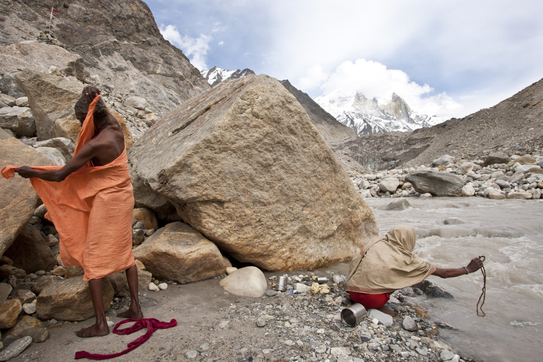 A pilgrim completes his personal ritual by dipping his mala in the sacred river while the other dresses after taking a bath.