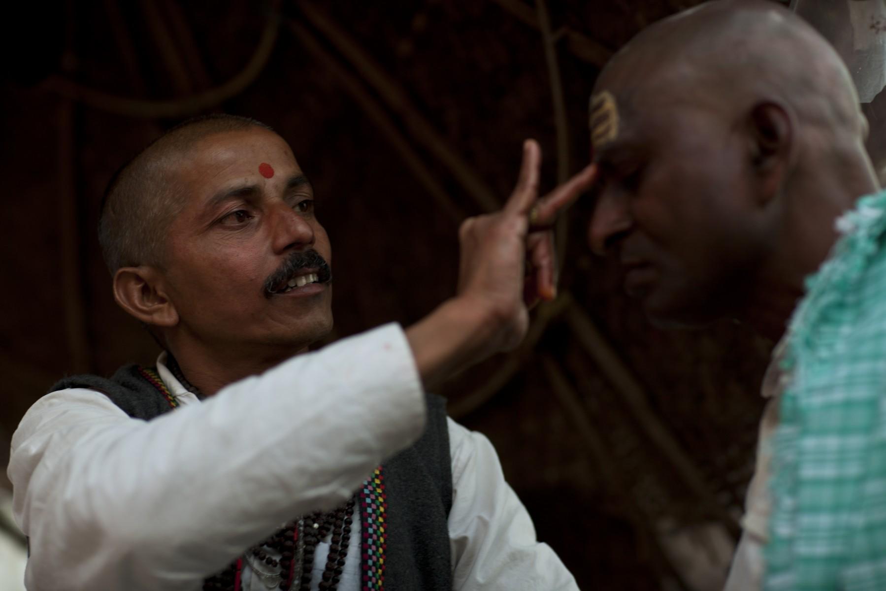 Priest blesses a pilgrim with a tika