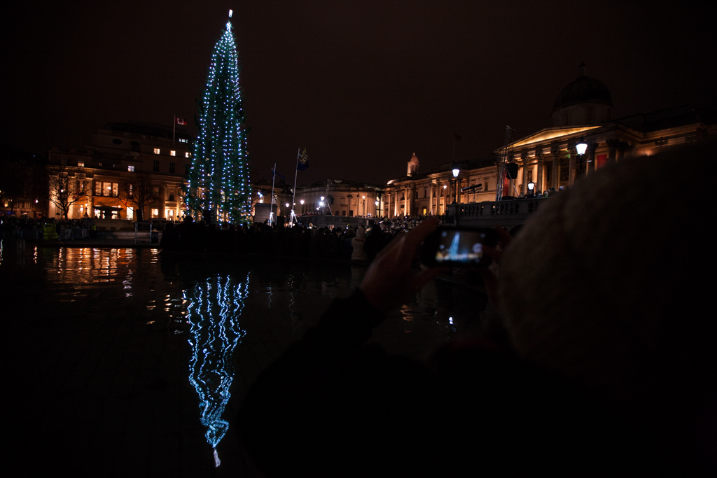 A large crowd in Trafalgar Square watch the traditional Christmas tree lighting ceremony. The tree is an annual gift from the people of Norwy for their apreciation of Britain's support during World War II